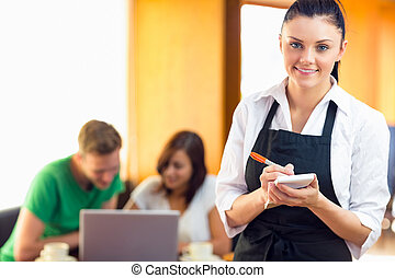 Portrait of a beautiful waitress writing an order with two...