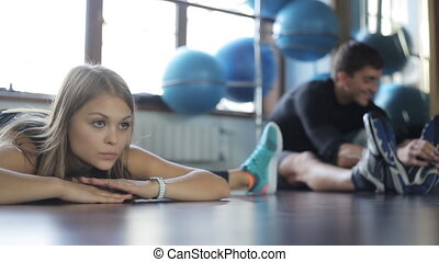 portrait of a beautiful woman athlete falls easily on the string near its male student. it is a fitness instructor trainer.