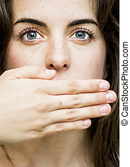 Portrait of a beautiful woman  covering her mouth with her hand on black background