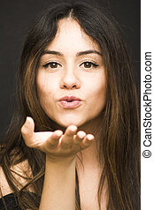 Portrait of a beautiful woman Giving a kiss to the air on black background