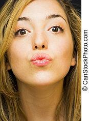 Portrait of a beautiful woman giving an air kiss