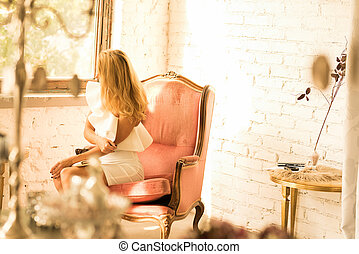 Portrait of a beautiful woman in a antique armchair