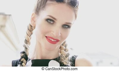 Portrait of a beautiful woman in a dress with long pigtails