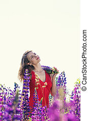 Portrait of a beautiful woman in a field of lupines