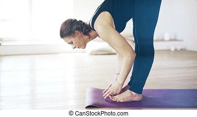 Portrait of a beautiful woman in black doing yoga indoors, side veiw