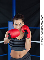 Portrait of a beautiful woman in red boxing gloves