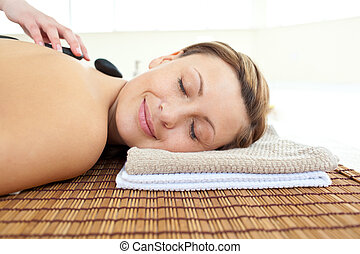 Portrait of a beautiful woman lying on a massage table with hot stones in a health spa