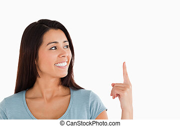 Portrait of a beautiful woman pointing at a copy space