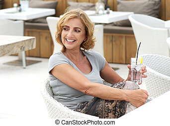 Portrait of a beautiful woman relaxing outside with a drink of water