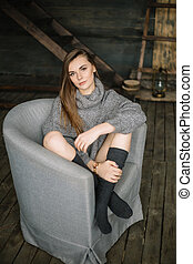 Portrait of a beautiful woman sitting cross-legged on the grey armchair wearing gaiters and long grey knitted cozy sweater. Sad serious girl in dayligth studio home posing.