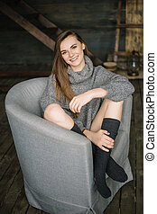 Portrait of a beautiful woman sitting cross-legged on the grey armchair wearing gaiters and long grey knitted cozy sweater. Happy girl in dayligth studio home posing.