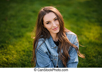 Portrait of a beautiful woman sitting on the green grass in the autumn park
