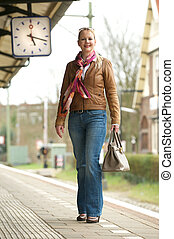Portrait of a beautiful woman smiling on train station platform