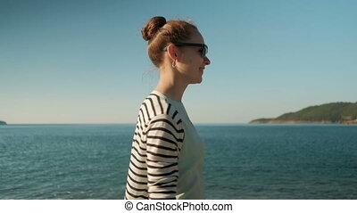 Portrait of a beautiful woman walking on a sunny beach.