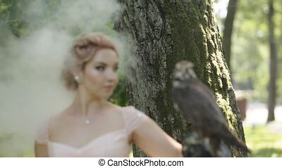 Portrait of a beautiful woman wearing with big eagle falcon on arm at foggy forest