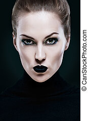 Portrait of a beautiful woman, with black lips. On a black background