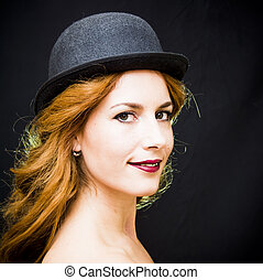 Portrait of a beautiful woman with hat on black background