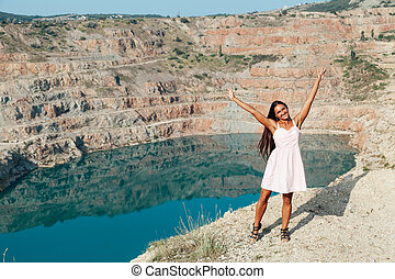 portrait of a beautiful woman with long hair in a dress on a cliff by the lake