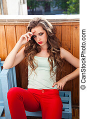 Portrait of a beautiful woman with long hair sitting on the floor