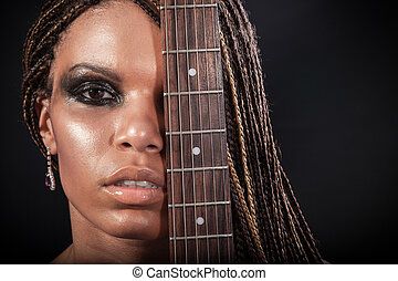 Portrait of a beautiful young african american woman with dreadlocks hair with an electric guitar on a black background