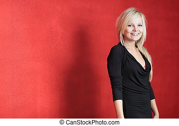 Portrait of a beautiful young blonde woman posing in front of a red wall