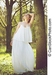 Portrait of a beautiful young bride in white wedding dress posing against tree