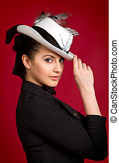 portrait of a beautiful young brunette girl in a white hat on a red background