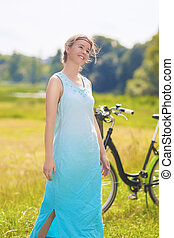 Portrait of a Beautiful Young Caucasian Woman Resting with Her Bike Outdoors. Vertical Image Composition