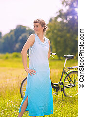Beautiful Young Caucasian Woman Resting with Her Bike Outdoors