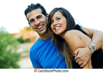 Portrait of a beautiful young couple smiling together -...