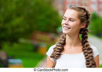 portrait of a beautiful young girl in a white T-shirt with two braids in the park