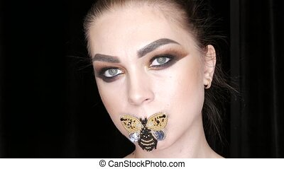 Portrait of a beautiful young girl model with fashionable smoky eyes makeup and a butterfly on her lips posing in front of the camera in studio. High-fashion