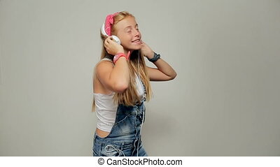 Portrait of a beautiful young girl (woman) listening to music, dancing