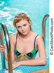 portrait of a beautiful young model in a pool near the stairs