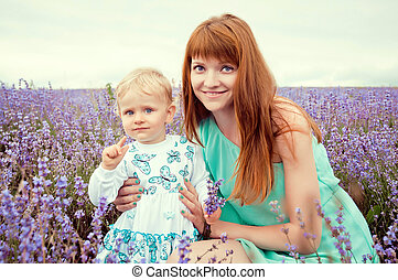 portrait of a beautiful young mother and child in nature