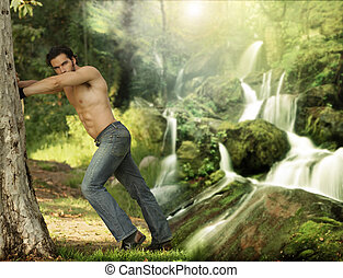 Portrait of a beautiful young muscular man leaning against a tree in a beautiful, heavenly place