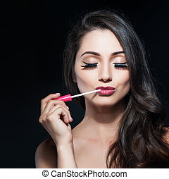 portrait of a beautiful young woman applied lip gloss