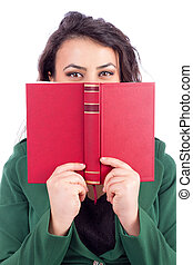 Portrait of a beautiful young woman holding a book in front of her face over white background