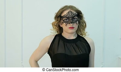 Portrait of a beautiful young woman in a black mask. Slow motion