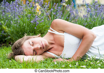 Portrait of a beautiful young woman in a white summer dress lying on a meadow
