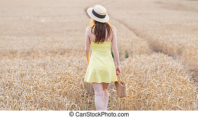 Portrait of a beautiful young woman in a yellow dress walking through the wheat field