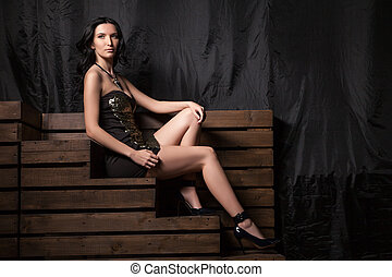 beautiful young woman in fashionable black dress sitting on stairs
