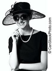 Portrait of a beautiful young woman in retro style in an elegant black hat and large sunglasses