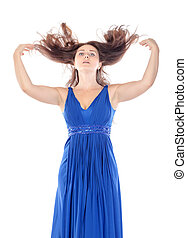 Portrait of a beautiful young woman in blue dress with streaming hair on white background