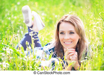 Portrait of a beautiful young woman lying in the grass