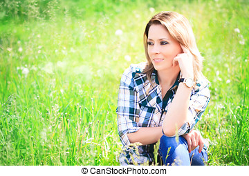 Portrait of a beautiful young woman sitting in the grass