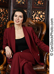 Portrait of a beautiful young woman sitting on chair