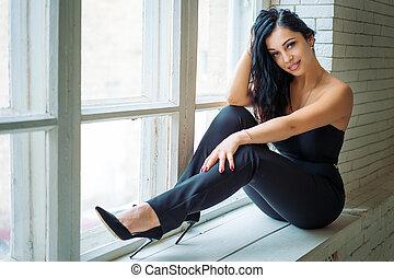 portrait of a beautiful young woman sitting on the windowsill