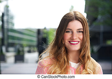 Portrait of a beautiful young woman smiling in the city