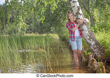 Portrait of a beautiful young woman standing in the water the la